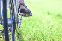 El pie de la mujer en pedal de la bicicleta en el primer de la hierba verde Fotografía de archivo