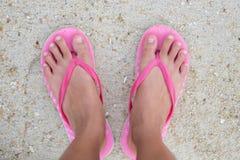 El pie de la mujer que lleva la sandalia rosada que se coloca en la playa de la arena es CCB Foto de archivo libre de regalías