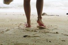 El pie de la mujer que lleva la sandalia rosada que se coloca en la playa de la arena es CCB Fotografía de archivo
