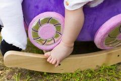 El pie del bebé minúsculo en caballo mecedora del juguete Foto de archivo libre de regalías