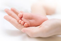 El pie del bebé recién nacido minúsculo en la mano femenina imágenes de archivo libres de regalías