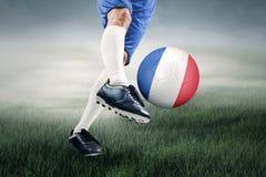 El pie golpea una bola con el pie en el campo Fotografía de archivo libre de regalías