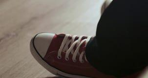 El pie humano en zapatillas de deporte rojas batió un golpe metrajes