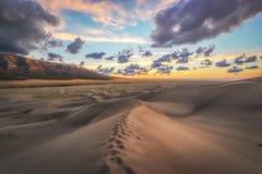 El pie imprime en una duna de arena en la puesta del sol foto de archivo