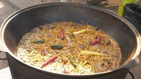 El pilaf nacional del plato del Uzbek en una caldera grande del arrabio en el fuego, cortó zanahorias amarillas, añadió el bérber almacen de metraje de vídeo
