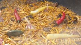 El pilaf nacional del plato del Uzbek en una caldera grande del arrabio en el fuego, cortó zanahorias amarillas, añadió el bérber almacen de video
