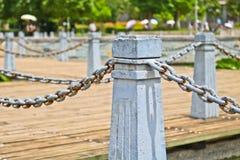 El pilar y la cadena cercan abajo en un lado del lago Imágenes de archivo libres de regalías