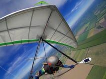 El piloto de planeador de caída se eleva las corrientes aéreas ascendentes termales arriba sobre terreno Fotos de archivo