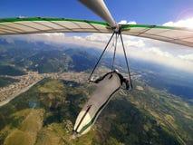 El piloto de planeador de caída vuela arriba sobre terreno alpino durante hangglid Foto de archivo libre de regalías