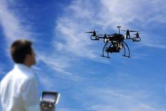 El piloto está volando el abejón con la cámara con el cielo azul y se nubla el fondo Imagenes de archivo