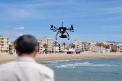 El piloto está volando el abejón con la cámara con el fondo costero Imagenes de archivo