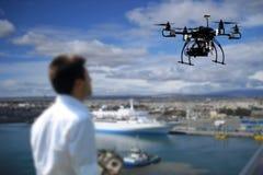 El piloto está volando el abejón con la cámara con el fondo costero Fotos de archivo libres de regalías