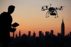 El piloto está volando el abejón con la cámara con el fondo de la ciudad del horizonte Imagenes de archivo