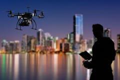 El piloto está volando el abejón con la cámara con el fondo de la ciudad del horizonte Imagen de archivo libre de regalías
