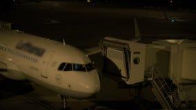 El piloto limpia el parabrisas de la cabina de su avión antes de salida del aeropuerto en la noche almacen de video