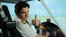 El piloto serio que hace los pulgares sube gesto en la cámara, recomendando línea aérea confiable metrajes