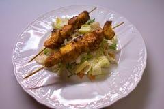 El pincho del curry del pollo sirvió en el top de ensalada vegetal hecho de lechuga y de otra Imagenes de archivo