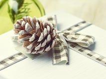 El pinecone y la cinta del pino adornan la caja de regalo de la Navidad en vagos verdes Imagen de archivo