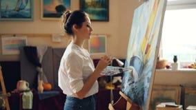 El pintor bonito de la mujer está representando el paisaje marino después que mira sus ilustraciones y que sonríe disfrutando de  metrajes