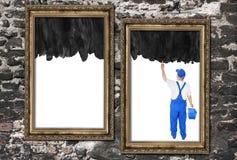 El pintor de casas cubre dos marcos vacíos Imagenes de archivo