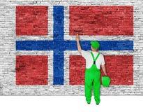 El pintor de casas cubre la pared con la bandera de Noruega Imagenes de archivo