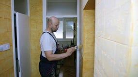 El pintor de casas pinta la pared con el cepillo Fotos de archivo libres de regalías