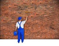 El pintor de casas pinta la pared de ladrillo Imagenes de archivo