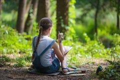 El pintor de la muchacha pinta árboles en el parque Fotografía de archivo libre de regalías