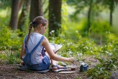 El pintor de la muchacha pinta árboles en el parque Foto de archivo libre de regalías