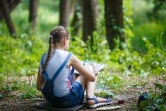 El pintor de la muchacha pinta árboles en el parque Fotos de archivo libres de regalías