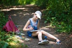 El pintor de la muchacha pinta árboles en el parque Foto de archivo