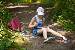 El pintor de la muchacha pinta árboles en el parque Fotos de archivo