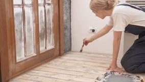 El pintor de la mujer en uniforme colorea el piso en el apartamento almacen de metraje de vídeo
