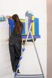 El pintor de sexo femenino adorna la pared, realizando tarea Imagen de archivo libre de regalías