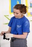 El pintor de sexo femenino adorna la pared, realizando tarea Fotografía de archivo libre de regalías