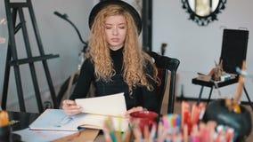 El pintor de sexo femenino colorea bosquejos almacen de metraje de vídeo