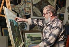 El pintor mayor con la barba y los vidrios dibuja una imagen de las flores por la pintura de aceite en taller del arte fotos de archivo