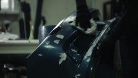 El pintor pinta un coche de parachoques en el taller de reparaciones almacen de video