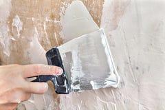 El pintor puttied la pared usando un raspador de la pintura, primer de la mano foto de archivo libre de regalías