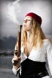 El pirata de la muchacha sopla un humo de una pistola vieja Imágenes de archivo libres de regalías