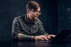 El pirata informático barbudo en vidrios hace cortar la sentada detrás de un ordenador portátil fotos de archivo