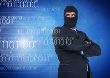 El pirata informático con la capilla y arma la situación cruzada encendido delante del fondo azul fotografía de archivo libre de regalías