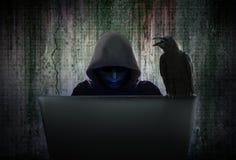 El pirata informático de ordenador en máscara negra y la capilla están cortando datos Imagen de archivo libre de regalías