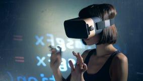 El pirata informático de sexo femenino utiliza los vidrios de VR mientras que agrieta el sistema, cierre para arriba almacen de metraje de vídeo