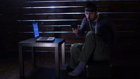 El pirata informático divertido cómico confía un ataque cibernético con un ordenador portátil y un arma en sus manos almacen de video