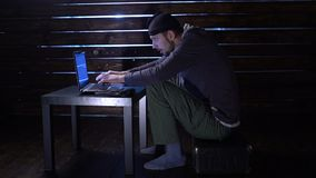 El pirata informático divertido cómico confía un ataque cibernético con un ordenador portátil y un arma en sus manos almacen de metraje de vídeo
