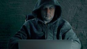El pirata informático en una sudadera con capucha se está sentando en la tabla en la noche y la codificación Hombre del pirata in metrajes
