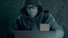 El pirata informático en una sudadera con capucha y vidrios que llevan se está sentando en la tabla en la noche y la codificación almacen de video