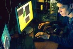 El pirata informático joven en la oscuridad infecta los ordenadores y los sistemas Foto de archivo libre de regalías