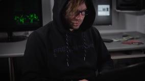 El pirata informático joven en un ordenador portátil crea un programa del virus para los ataques cibernéticos en el servidor del  metrajes